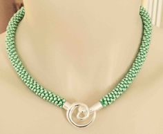 "Beaded kumihimo necklace.  Toho beads in icy green with front focal clasp, 16"".  N.stapleydesigns@gmail.com"