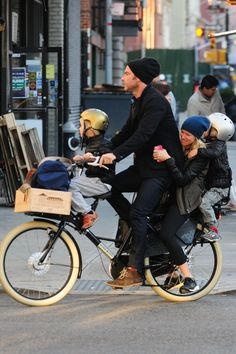 Liev Schreiber, Naomi Watts and family bike through the streets of New York City.