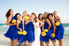 Bright blue bridesmaids dresses with yellow bouquets - great for a beach wedding // OneWed