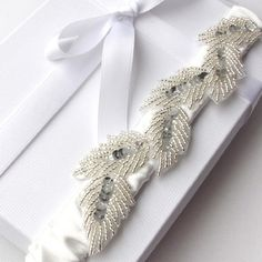The Athena Goddess pale ivory bridal garter is fashioned from sumptously soft and slinky silk satin; and is luxuriously embellished with a vintage hand-beaded and silver sequin laurel leaf applique. £39.99