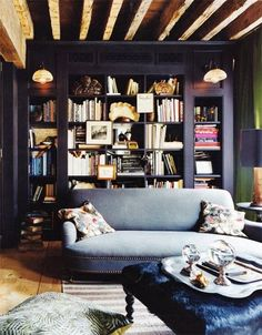 Another dark bookcase situation. We love the exposed beams, blackcents, lighting, knick knacks, art, cow hide ottoman, couch. What don't we love? The pillows. We would switch those out. Other than that, we would adore curling up to this bookcase and reading its contents.