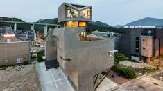 An angled concrete frame covers a large window at the top of this irregularly shaped housing block by South Korean architect Moon Hoon, who designed it to resemble an owl.