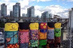 À l'occasion de la Biennale de Vancouver, les deux frères brésiliens connus sous le nom d'OSGEMEOS (pour retrouver le précédent article, cliquez ici) signent cette fresque aussi colorée que massive sur des silos dans une zone industrielle de Vancouver. Le premier défi de ce projet était de trouver un endroit qui conviendrait à leur idée. Ils ne voulaient pas d'un mur traditionnel en deux dimensions, ils voulaient quelque chose de différent, spécial et unique.