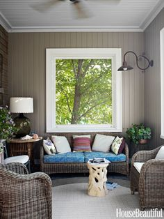 """Screened Porch: """"Inside the partially enclosed screened porch: an all-weather wicker sofa and chairs and a root-shape garden seat, all from Treillage, atop a Couristan indoor/outdoor rug."""""""
