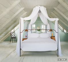 Dressed with IKEA curtains, a wrought-iron lit à polonaise with an eight-foot-tall canopy takes center stage in the master bedroom of Tom Scheerer's 200-year-old cottage on Harbour Island in the Bahamas. Painted in pastel green, the room is kept shady and cool by louvered shutters.