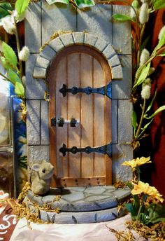 """Fairy door.  Pre-made wood door was textured, painted, and decorated, and mounted atop a wood """"book"""" box I decorated with decoupage and paint.  Spine of book slides out to reveal a drawer.   --Meggie"""