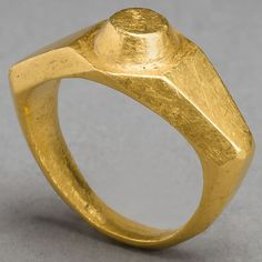 View 1: A massive Imperial Roman solid gold ring of angular wide shouldered style, a raised circular boss on the bezel. Intact, 3d - 4th Centuries AD, eastern Mediterranean.