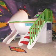 While we aren't a huge fan of the mural... who wouldn't want a rocket ship bed with slide!