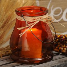 Add rustic charm to your fall decor with our Rounded Glass Lanterns, available in orange and brown. The raffia bow and warm colors make these lanterns welcoming and festive!