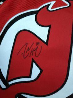 An Adam Henrique signed Devils logo.