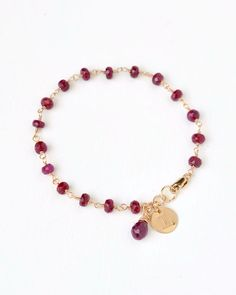 Faceted ruby beads are individually wire wrapped by hand to form this simple, elegant chain. It is adorned with a ruby briolette and gold disc charm. Personalize this gift by having her initial hand stamped on a gold filled charm.  Personalized birthstone jewelry by Blue Room Gems.