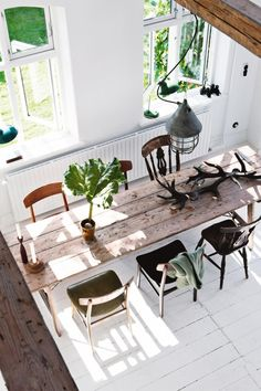 Dining room: long rustic timber dining table with six mismatched vintage chairs, white floorboards, long radiator