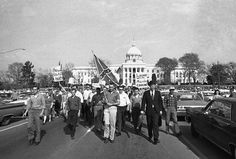 In this March 18, 1965 file photo, members of the Organization for Better Government march with a Confederate flag away from the capitol in Montgomery, Ala. They stopped within 25 feet of voter registration rallies, had several speeches, then marched off again.