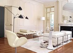 Mid Century interior in white, Arne Jacobsen's Swan chair (1958), Mouille's tripod floor lamp (c 1950's), Le Corbusier-Jeanneret Perriand LC2 armchairs (1928), Mies van der Rohe´s Barcelona daybed, (1930).