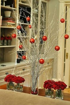 In a high-low arrangement, solid color ornaments match b the flowers. You could mix and match colors or have contrasting colors. This is very simple. You could also tie ribbons on the branches and wrap matching ribbon around the shorter vases.