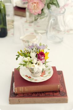 books with vintage looking tea cup set on top with a few flowers.  cute