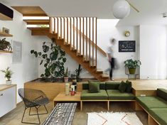 A planter is integrated under the open staircase leading to the upper floor, and a skylight in the roof illuminates the stairwell. #hometour #livingroom #stairs