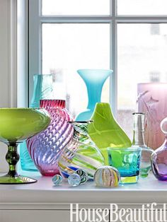 A glass collection glows on the windowsill.