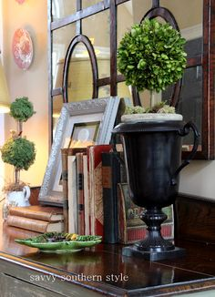 sweet vignette...ADORE the mirror and the topiaries!