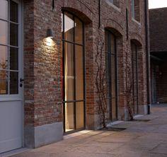 Concrete plinth, mellow brick + metal casement windows