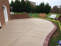 Stained concrete patio with a sprayed concrete brick border in ...