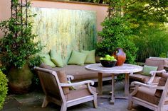 patio with wooden chair with brown cushion, wooden round table, plants in big pots, green paintings on the wall of Outdoor Decor to Make Your Garden Amazingly Finished