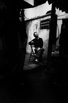 """As I was visiting my father in Shanghai, I was brought to a water village (sort of like a Venice of the east). There are often many tourists, foreign or local, that come to these villages to spend the day. Amidst the crowds, the local villagers remain indifferent to the visitors and go about their day to day lives, as does this man, simply relaxing until something catches his eye from above.     — By Jennifer Rimaz (from """"Open Theme"""")"""