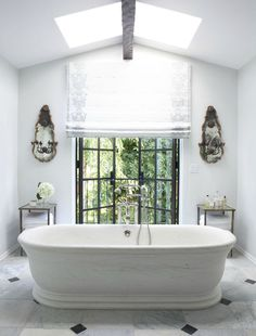 All white bathroom with stand alone soaker tub.