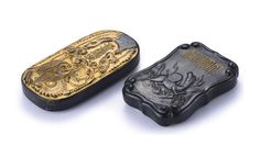 TWO SMALL MOULDED AND INSCRIBED GILT-DECORATED INK CAKES QING DYNASTY, KANGXI PERIOD comprising: a quatrefoil ink cake decorated with a horse prancing among waves under a gilt four-character inscription reading wen zi zhi zu ('the origins of calligraphy'), the reverse with the poem wang shi mao tian yi shi zhi, cang lung ye mo; and an ink cake of oval form gilded on one side with a dragon grasping a lingzhi in the mouth under the characters, cang lung ye, the reverse with sa wen he zi han…
