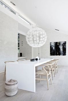 A close up of the dining room from the inside, showing the light pine dining chairs coupled with the white minimalist dining table. The walls are subtly painted brick in a light gray.