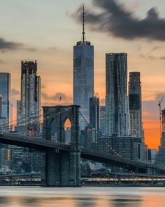 One world trade and the Brooklyn bridge standing tall during sunset