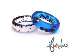 Set of 2 handcast resin rings. 1 ring is a transparent blue with silver flakes and irridescent blue glitter The other ring is clear with the irridescent blue glitter You will receive the 2 rings in the photos.  Ring size: Interior diameter 19mm- UK Q/R - US 8.5-9 Send me a message if you would like these rings in another size The ring is hand cast using high grade jewellery resin. Resin is a great alternative to glass, it is scratch resistant and can withstand being dropped or knocked ab...