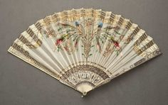 Folding fan of bone sticks with a silk leaf embroidered in bright satin-stitch, and encrusted with gold sequins. The short bone sticks are decorated with silver and gold leaf. French c1810. FAMSF