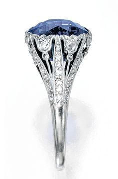 PLATINUM, SAPPHIRE AND DIAMOND RING, MARCUS & CO. Centered by a cushion-cut sapphire weighing approximately 8.95 carats, within a floral mounting set with old European and single-cut diamonds weighing approximately .95 carat, signed M & Co, circa 1925.
