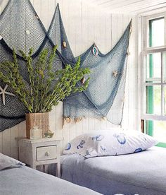 Hanging fishing nets and adding shells makes a fabulous focal point for this guest room