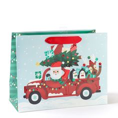 Santa is on his way to deliver presents in a truck with his reindeer and penguin friends on this gift bag. The red ribbon handles add the perfect finishing touch. Christmas Gift Bags, Christmas Shopping, Holiday Gifts, Christmas Cards, Xmas, Large Gift Bags, Christmas Tree Design, Christmas Characters, Jolly Holiday