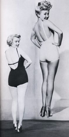 Marilyn Monroe stands next to Betty Grable's famous pin-up image