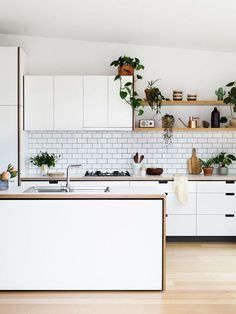 All-white kitchen with subway tile backsplash and wood open shelving.
