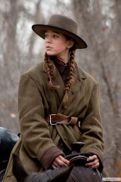 "Hailee Steinfeld, 'True Grit' (2010). Costume design by Mary Zophres. Zophres notes:  ""Mattie wears what was known as Stetson's Boss of the Plains hat, which was a wider brimmed hat popular in Texas.  Really, there were no true 'cowboy hats' in that period.  They were all city hats that looked different because they got completely messed up in the elements."""