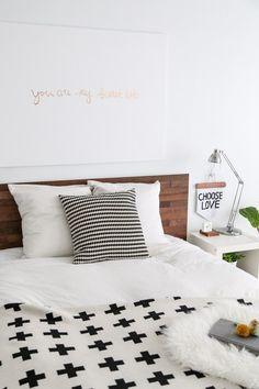 Weißes Bett von IKEA mit Holzverblendung zum Designerbett erheben.