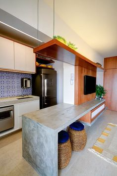 Cozinha integrada com sala. Bancada de concreto. Painel de madeira da tv de correr para fechamento cozinha. Azulejos azuis. Prateleira com cabo de aço, apoio na laje.
