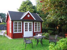 Vor dem Clockhouse Gartenhaus in Schwedenrot befinden sich gemütliche Gartenmöbel aus Gusseisen.  http://www.gartenhaus-gmbh.de/