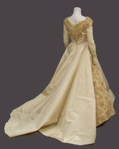 An AMAZING 1950's wedding gown in yard upon yard of cream silk taffeta. GORGEOUS ecru lace and tan tulle insets at the chest, shoulders and sides of skirt. Accented on the lace portions with clusters of faux pearls and tiny, subtle iridescent sequins. Long sleeves with pointed, buttoned wrists.
