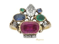 A very rare Georgian diamond, ruby, emerald and sapphire giardinetti ring. An important piece, set with an oval old mine diamond in a closed back silver cu...