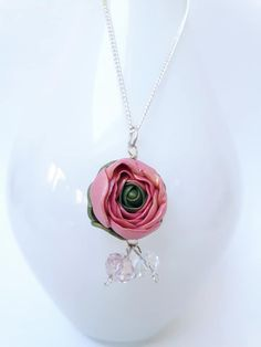 A pink rosebud pendant created using polymer clay and handcrafted into a rosebud shape. Pink and white crystals dangle to catch the light. Empowered with Reiki energy. Hung from a 30 inch silver chain. Handcrafted here in my studio in Cork City, Ireland Cork City, Irish Design, Reiki Energy, Polymer Clay Jewelry, Rose Buds, Ireland, Jewelery, Dangles, Handmade Jewelry