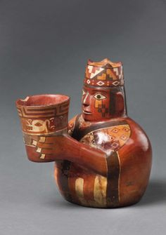 """Cup-Holding Figure in Tie-Dyed Tunic and Four-Cornered Hat Peru, 600–1000 Ceramic and slip Museo Regional de Ica """"Adolfo Bermúdez Jenkins,"""" Ica, Peru"""
