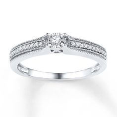 This promise ring for her features a sparkling diamond as its focal point and a band festooned in more diamonds. Milgrain detailing adds a vintage touch to the sterling silver ring, which has a total diamond weight of 1/8 carat. Diamond Total Carat Weight may range from .115 - .14 carats.