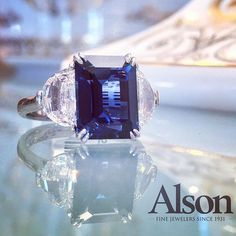 Swoon!  Stunning 5.51 emerald cut sapphire accented with half moon diamonds.