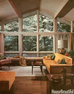 In a large living room, the main grouping of furniture is isolated from all through traffic. A low bench provides extra seating without turning focus away from the featured view into the treetops outside. Restrained drapery and furniture fabrics in green and gold harmonize with wood and cane of furniture and with outdoor scene. Featured in the October 1960 issue.   - HouseBeautiful.com