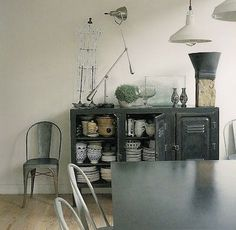 Metal lighting fixtures and an industrial cupboard used as a credenza.